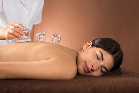 39653874 - young female lying on front receiving cupping treatment on back