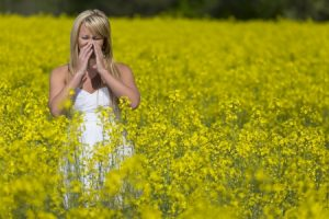 19238500 - a blonde model in a field of flowers with allergies